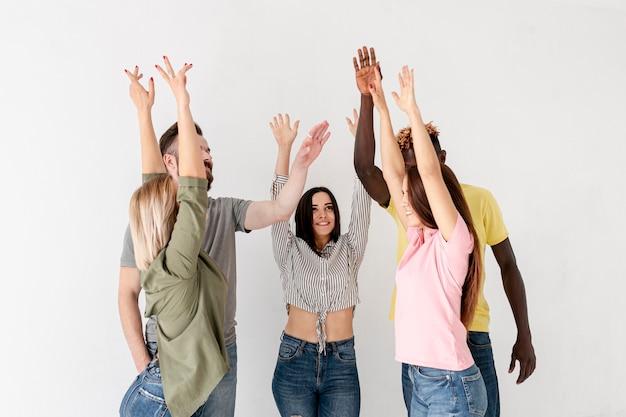 Vista frontal jovens amigos com as mãos levantadas Foto gratuita