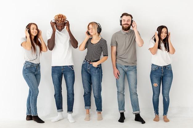 Vista frontal jovens com fones de ouvido Foto gratuita