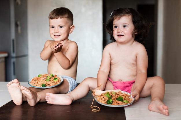 Vista frontal jovens irmãos na cozinha Foto gratuita