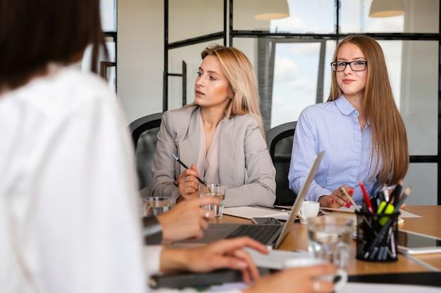 Vista frontal jovens mulheres no trabalho Foto gratuita