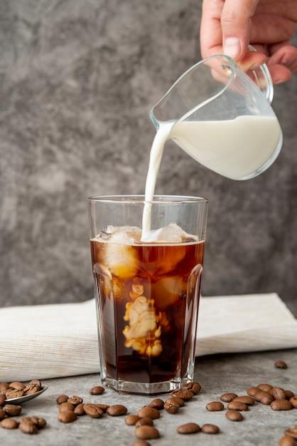 Vista frontal, leite, despejado, em, café gelado Foto gratuita