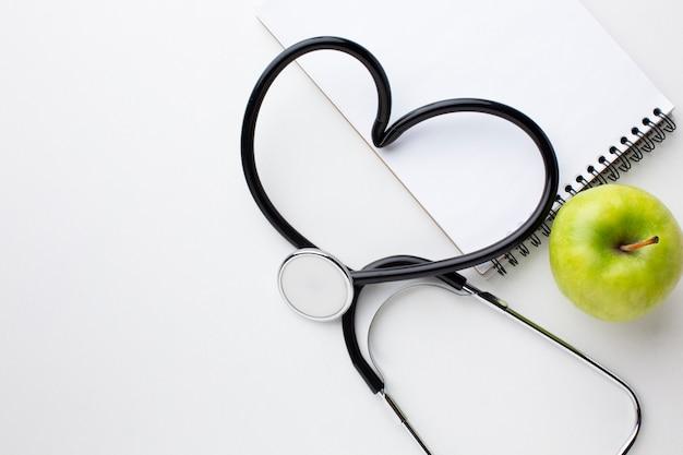 Vista frontal maçã verde e estetoscópio em forma de coração Foto gratuita