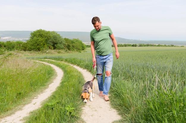 Vista frontal macho adulto indo passear com seu cachorro Foto gratuita