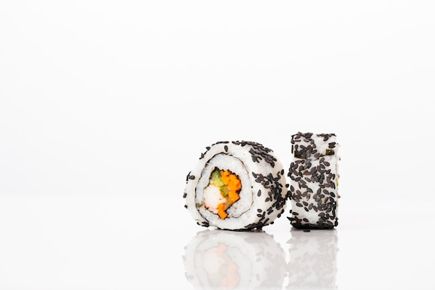 Vista frontal maki sushi rolos com sementes de gergelim preto Foto gratuita