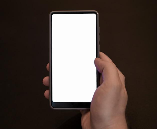 Vista frontal mão segurando o modelo de telefone Foto gratuita