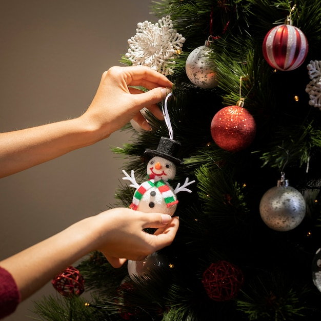Vista frontal mãos colocando globos na árvore de natal Foto gratuita