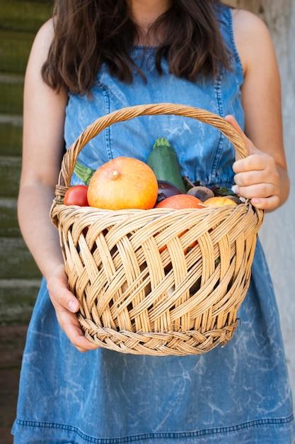 Vista frontal mãos segurando cesta com legumes Foto gratuita