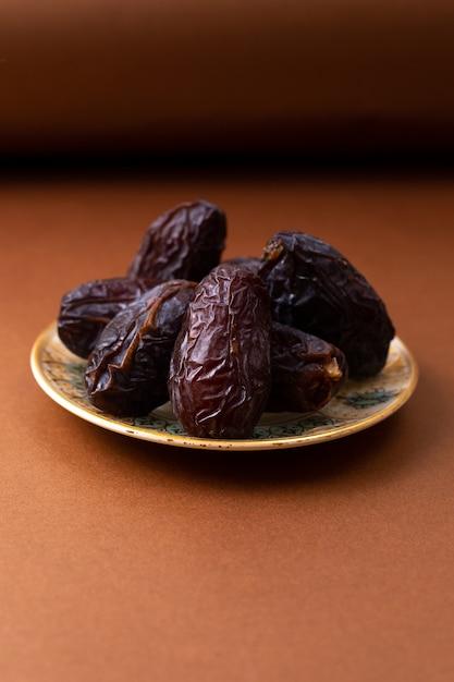 Vista frontal marrom xurma doce saboroso dentro da placa na mesa de madeira marrom Foto gratuita