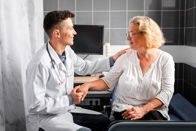 Vista frontal médico segurando a mão do paciente Foto gratuita