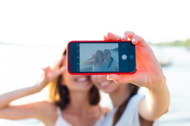 Vista frontal melhores amigas tirando uma selfie Foto gratuita