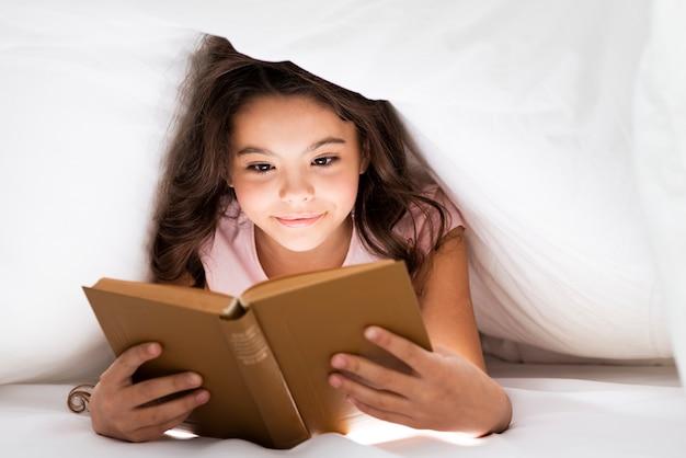 Vista frontal menina bonitinha lendo Foto gratuita
