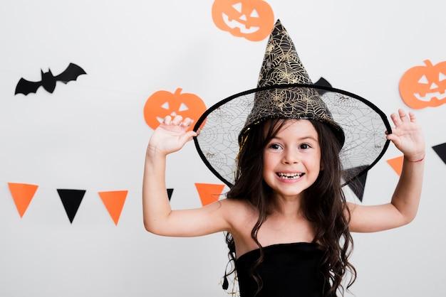Vista frontal menina fantasiada de bruxa para o halloween Foto gratuita