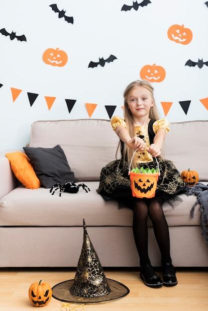 Vista frontal menina fantasiada de bruxa Foto gratuita