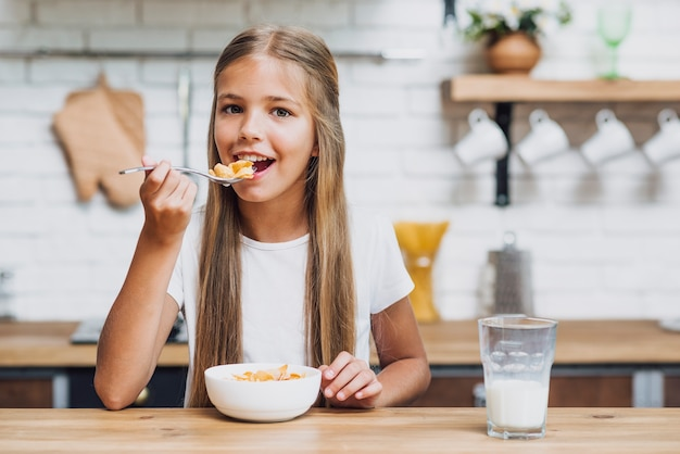 Vista frontal menina loira comendo seus cereais Foto gratuita