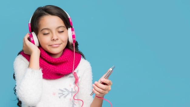 Vista frontal menina ouvindo música Foto gratuita