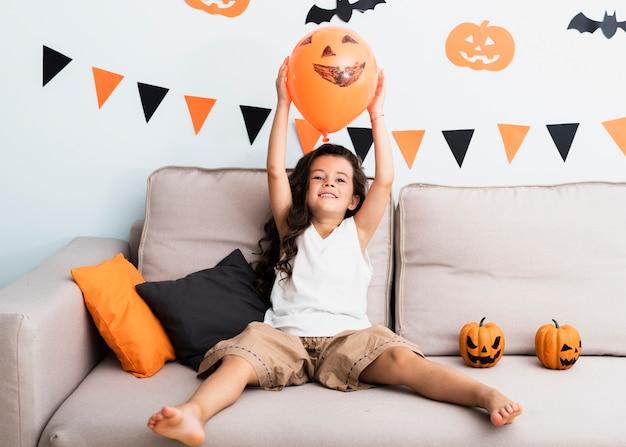 Vista frontal menina segurando um balão de halloween Foto gratuita