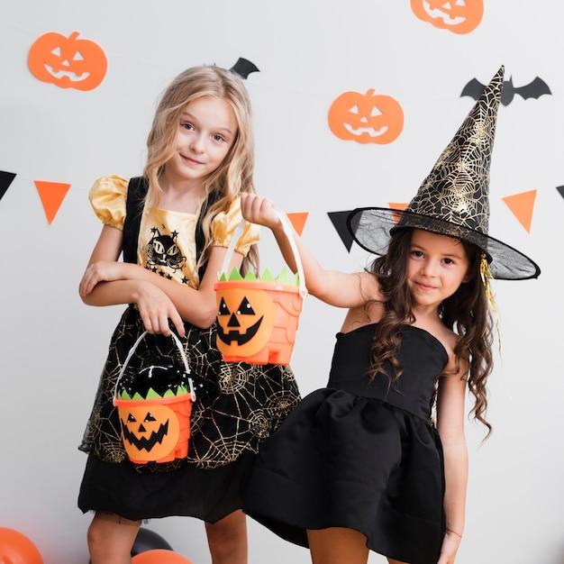 Vista frontal meninas na fantasia de bruxa para o halloween Foto gratuita