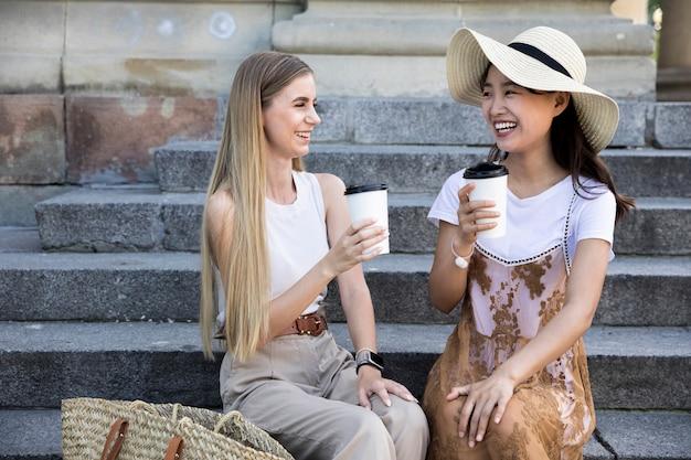 Vista frontal meninas tomando uma xícara de café Foto gratuita