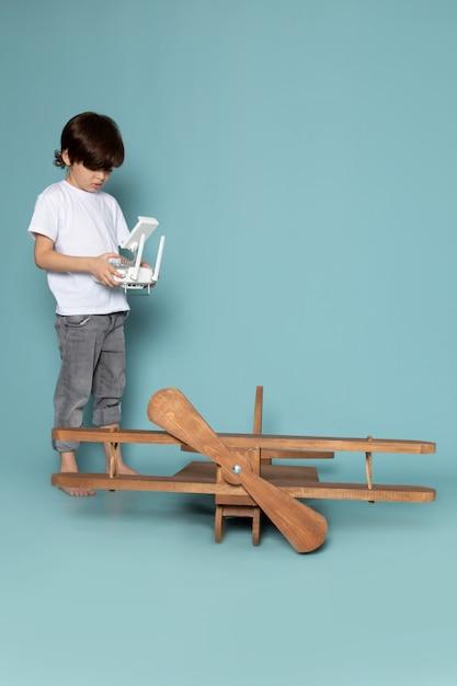 Vista frontal menino bonitinho adorável controlando o avião de madeira sobre a mesa azul Foto gratuita