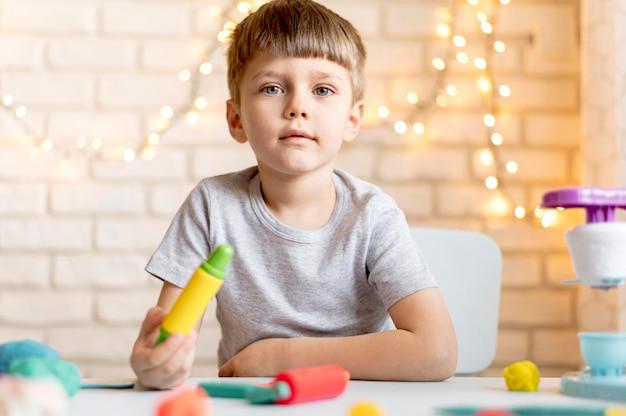 Vista frontal menino brincando com brinquedos Foto gratuita