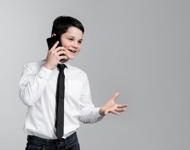 Vista frontal, menino jovem, falando telefone móvel Foto gratuita