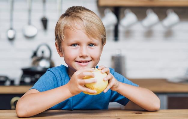 Vista frontal menino loiro comendo uma maçã Foto gratuita