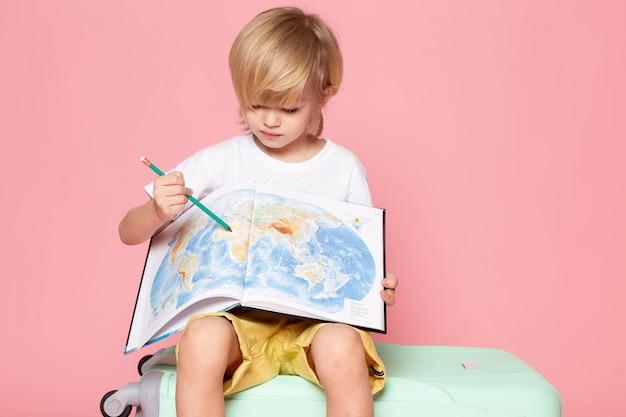 Vista frontal, menino loiro, desenho, mapa, em, camiseta branca, chão rosa Foto gratuita