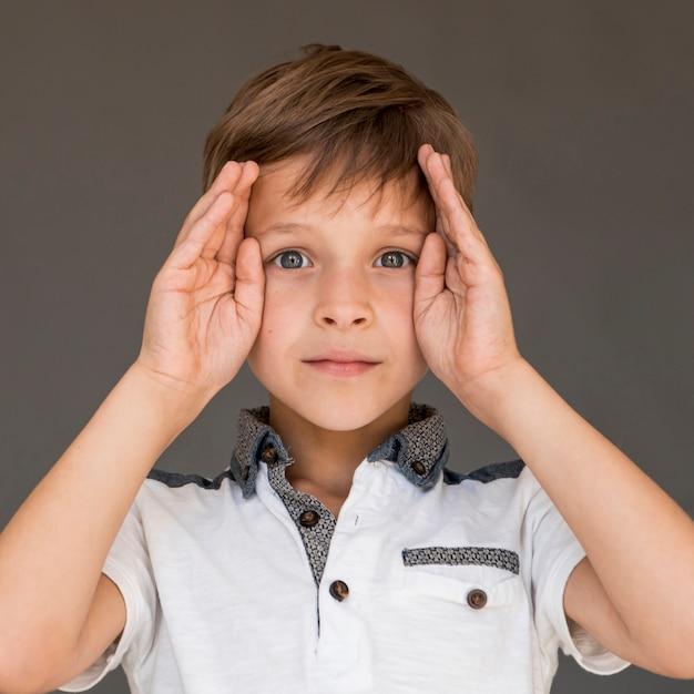Vista frontal menino olhando confuso Foto gratuita