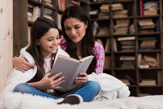 Vista frontal mulher adulta e menina lendo um livro Foto gratuita