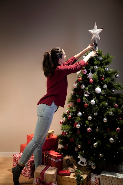 Vista frontal mulher colocando na árvore de natal a estrela Foto gratuita