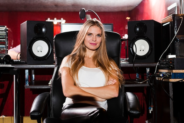 Vista frontal mulher com braços cruzados sentado em um estúdio Foto gratuita