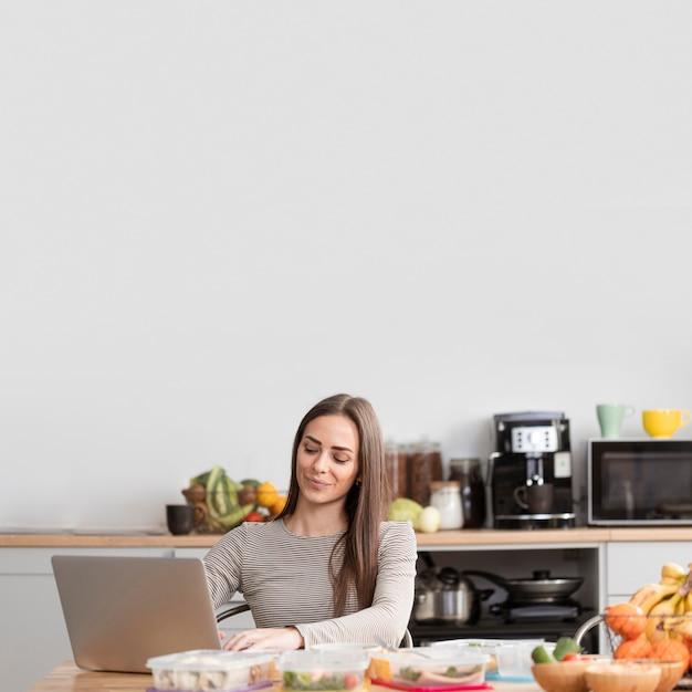 Vista frontal mulher com comida e computador portátil Foto gratuita