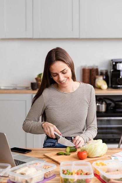 Vista frontal mulher cortando o jantar no trabalho Foto gratuita