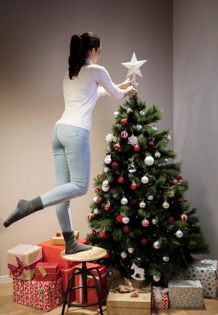 Vista frontal mulher decorando a árvore de natal Foto gratuita