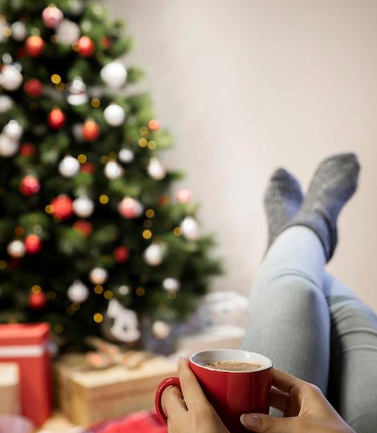 Vista frontal mulher em casa bebendo chá na época do natal Foto gratuita