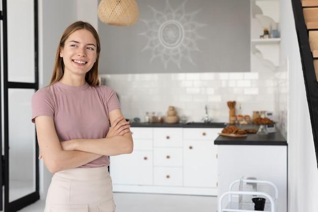 Vista frontal mulher em pé na cozinha Foto gratuita
