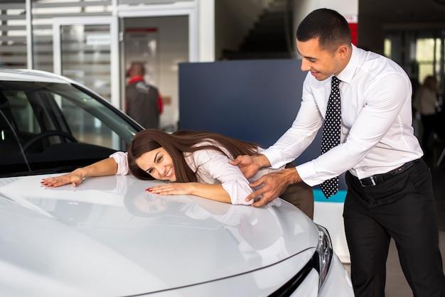 Vista frontal mulher encostada no carro e macho pegá-la Foto gratuita