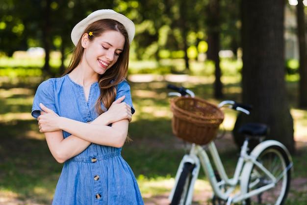 Vista frontal mulher feliz com bicicleta Foto gratuita