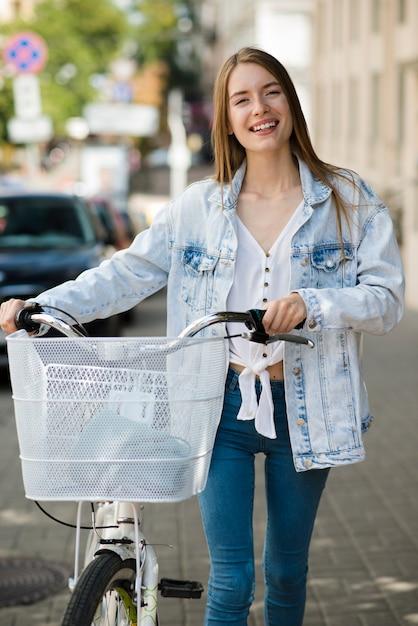 Vista frontal mulher feliz com sua bicicleta Foto gratuita