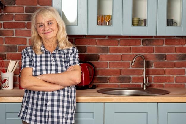 Vista frontal mulher idosa na cozinha Foto gratuita