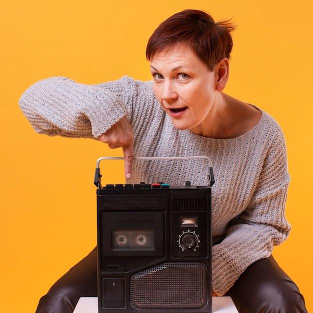 Vista frontal mulher idosa segurando o toca-fitas vintage Foto gratuita