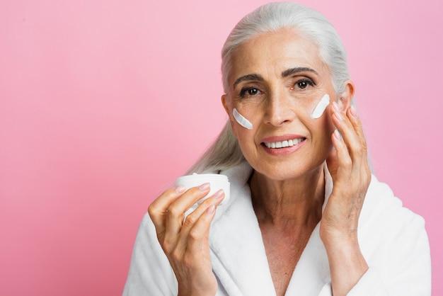 Vista frontal mulher idosa teste hidratante Foto gratuita