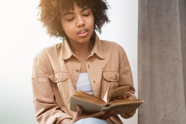 Vista frontal mulher lendo um livro Foto gratuita