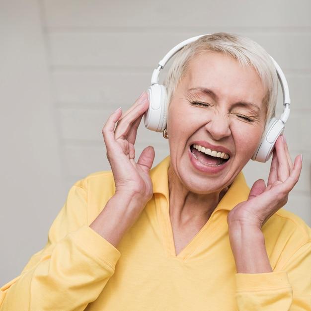 Vista frontal mulher madura ouvindo música Foto gratuita