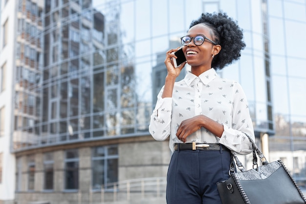 Vista frontal mulher moderna falando ao telefone Foto gratuita