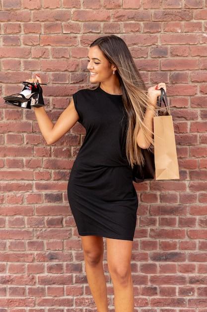 Vista frontal mulher mostrando seus sapatos novos Foto gratuita