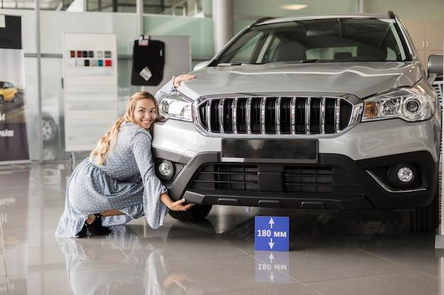 Vista frontal mulher posando ao lado de um carro Foto gratuita