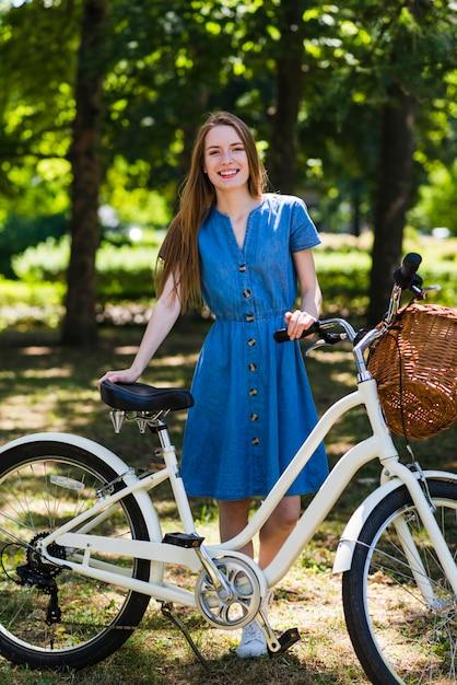 Vista frontal, mulher, posar, com, dela, bicicleta Foto gratuita