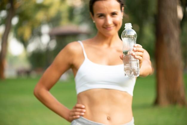 Vista frontal mulher segurando a garrafa de água Foto gratuita