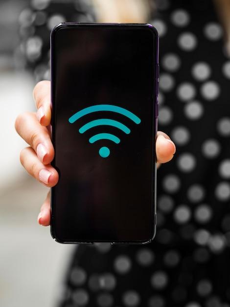 Vista frontal mulher segurando o telefone com o símbolo de wifi na tela Foto gratuita